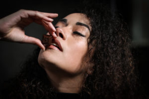 An image of a female model with curly hair indulging in a piece of Nove luxury chocolates.
