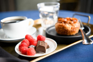 Nove cannabis-infused luxury chocolates resting on a small plate with raspberries; the plate rests on a breakfast tray. Discover your edible ritual.