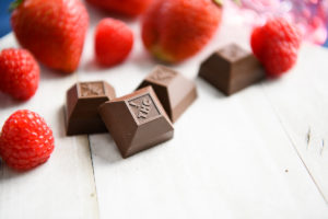 Nove Raspberry Bramble bar next to fresh raspberries and strawberries on a white surface. Nove chocolates are one of the Best Cannabis Gifts for Mom