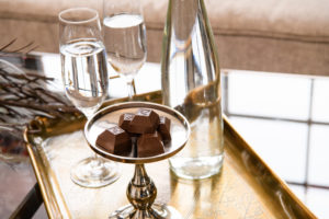 Nove luxury cannabis chocolates on a gold platter next to a decanter and champagne flutes. Enjoy wine and cannabis chocolates this National Wine Day!