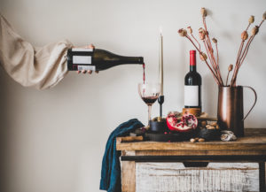 Red wine, board with cheese, fruit, almonds and olives, candles, decorative flowers on kitchen counter and womans hand pouring wine to glass, white wall at background. Winery, wine tasting concept