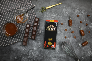 Nove Sea Salt Caramel on a metal surface, surrounded by caramel candies and other kitchen equipment.