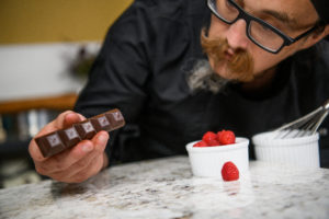 Medically Correct Co-Founder and Executive Chef, Josh Fink, is examining a Nove luxury cannabis chocolate bar.