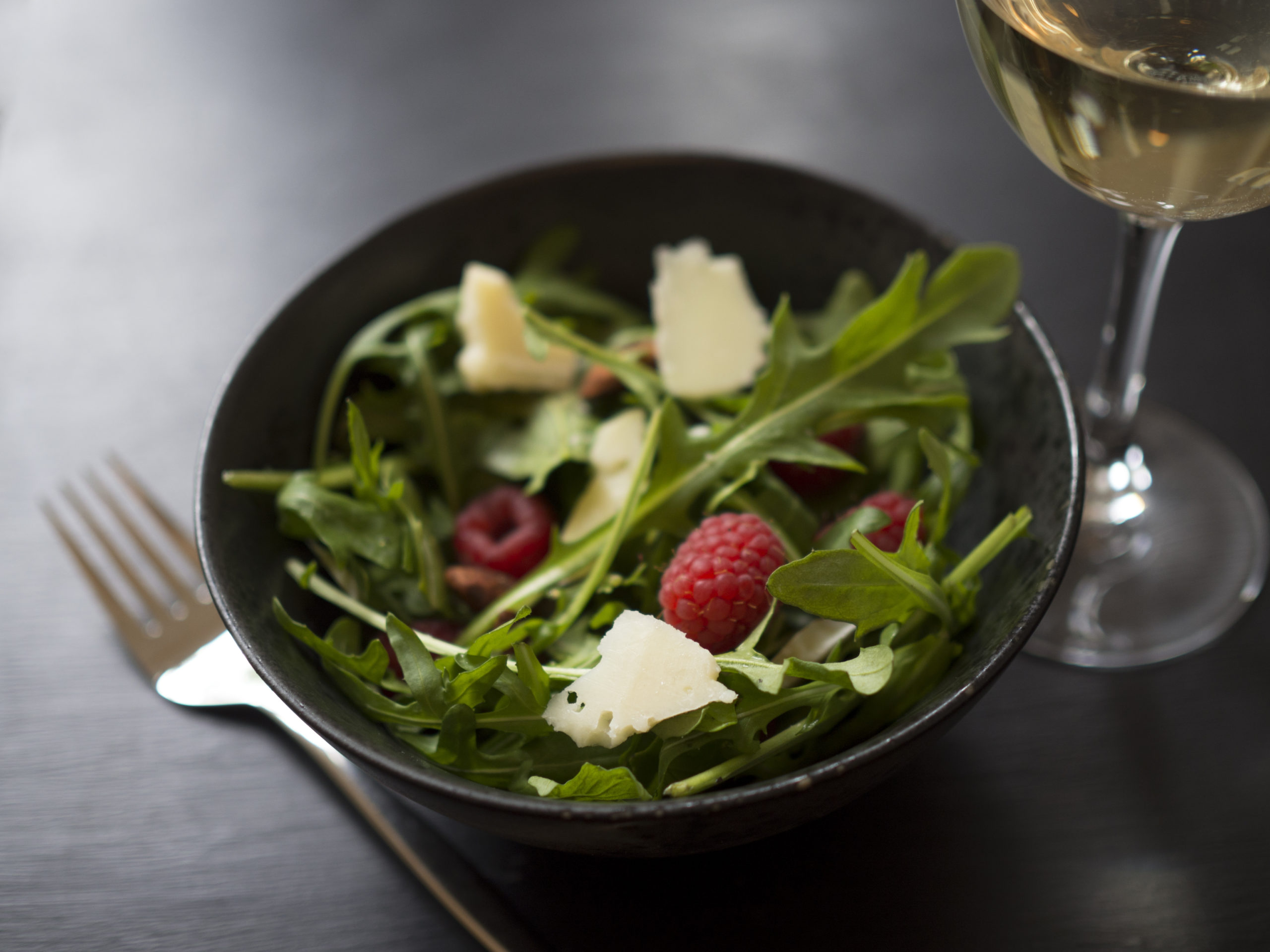 A rocket salad topped with parmesan, almonds, and raspberries. The infused Raspberry Chocolate Salad by Nove is a must-try.