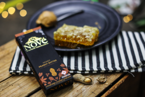 Nove Honey Peanut Butter cannabis chocolate resting next to fresh honeycomb and peanuts.