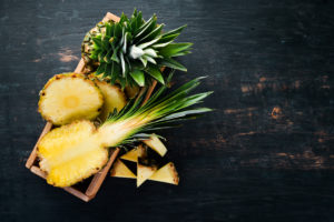Pineapple. Sliced pineapple on a wooden background. Top view. Free copy space.