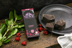 Nove Raspberry Bramble chocolate bar resting on a wood surface, surrounded by raspberries and chunks of chocolate.
