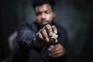 A young black man holding a piece of Nove Cafe Cappuccino cannabis-infused chocolate up close to the camera.