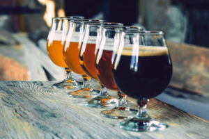 Glasses of different kinds of dark and light beer on wooden table in line. Cold delicious drinks are prepared for a big friend's party. Concept of drinks, fun, meeting, oktoberfest.