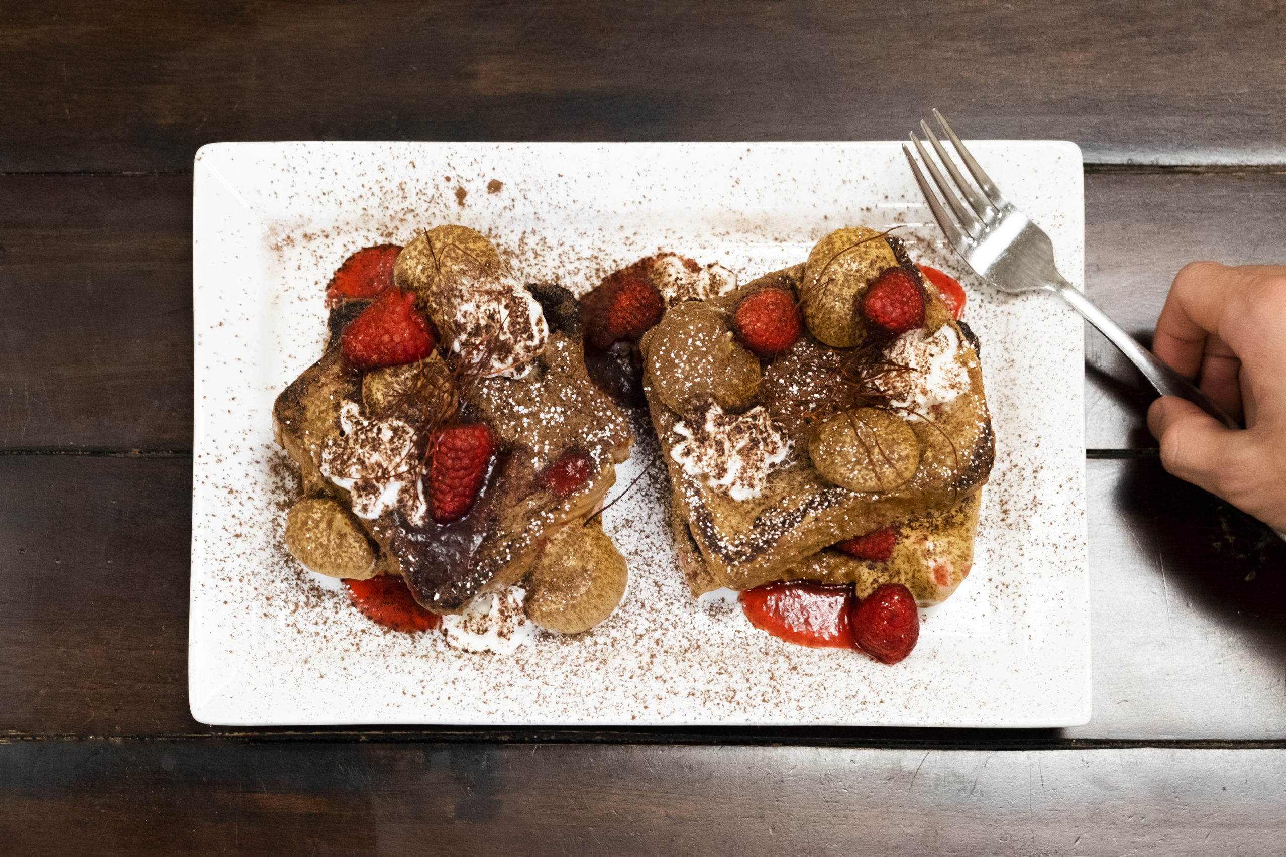 French toast on a white plate, topped with cannabis-infused dalgona coffee cream and spicy raspberry coulis.