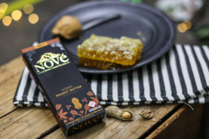 A Nove Honey Peanut Butter bar resting on a striped, cloth napkin.  This is one of the key ingredients when making our cannabis-infused pumpkin bread.