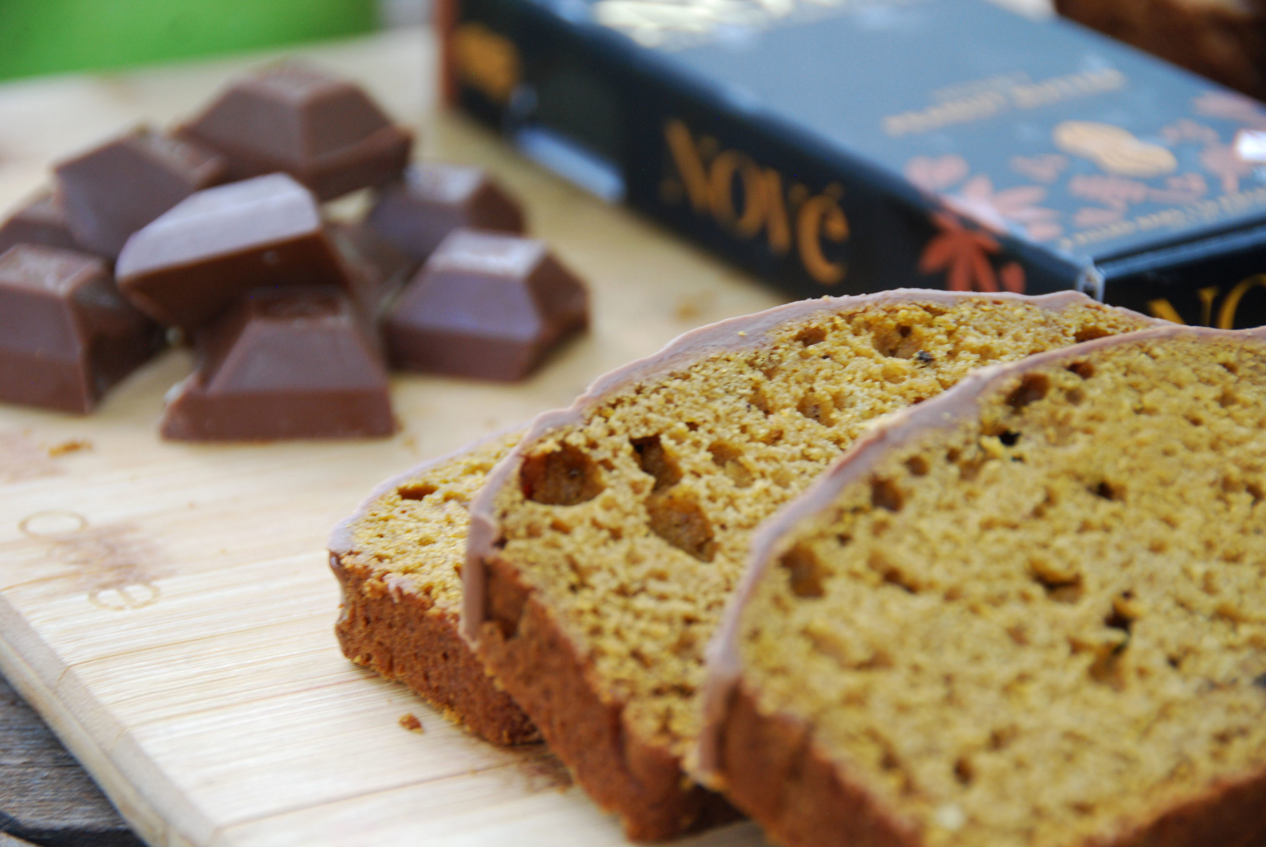 Cannabis-Infused Pumpkin Bread slices resting on a wood surface next to a Nove Honey Peanut Butter bar.