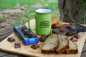 A green, Fresh Baked Dispensary-branded mug next to two Nove Luxury Edibles chocolate bars.
