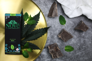 An image of Nove Luxury Edibles Glacier Mint chocolate bar resting on a gold tray surrounded by chocolate and mint leaves.