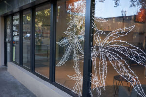 A shot of line-drawn cannabis leaves, posted to the outside windows of a dispensary.  Retail workers in the cannabis space are incredible; read nine things budtenders do that most people don't realize.